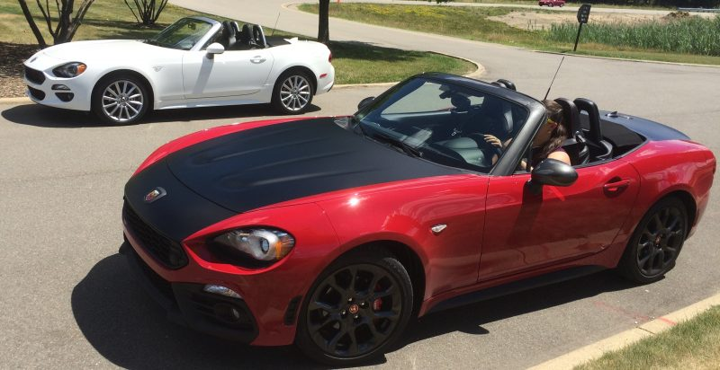 Red Fiat 124 Spider Abarth (front) and white Fiat 124 Spider (rear).